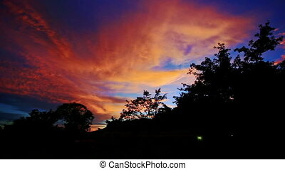 Orange Sunset Clouds in Dark Blue Sky over Tropical Forest -...
