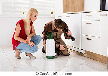 Woman Looking At Male Worker Spraying Insecticide