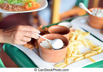 Woman's hand serving food from traditional Brazilian lunch...