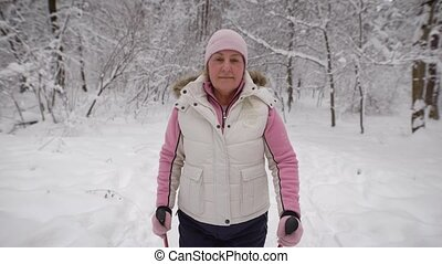 elderly woman in a beautiful sports wear is engaged in Nordic walking on  snowy path in winter forest. Modern pensioner actively pursuing their leisure time outdoors.