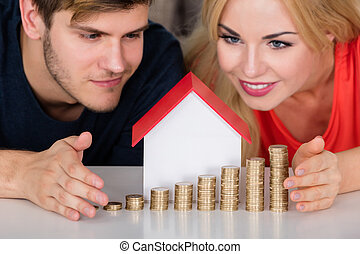Couple Protecting House Model With Stacked Coins - Young...
