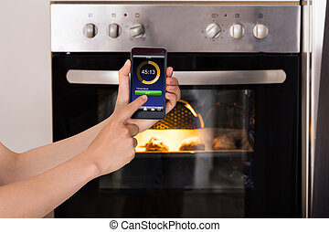 Person Operating Oven Appliance With Mobile Phone - Close-up...