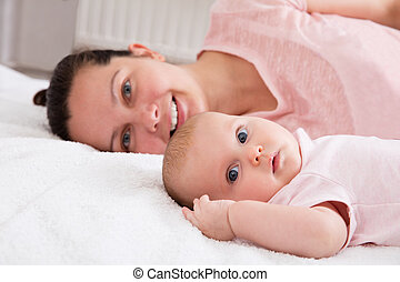 Woman With Baby On Bed