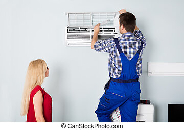 Technician Repairing Air Conditioner At Home - Woman Looking...