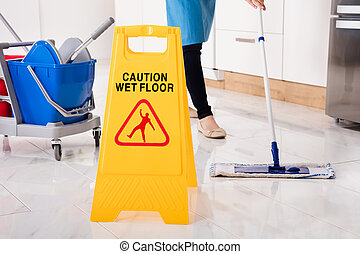 Yellow Wet Caution Sign On Wet Floor In Kitchen