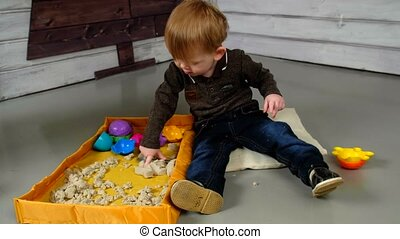 Little boy playing with wooden railway on the floor.