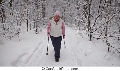 The elderly woman spends the leisure-time in the wood....
