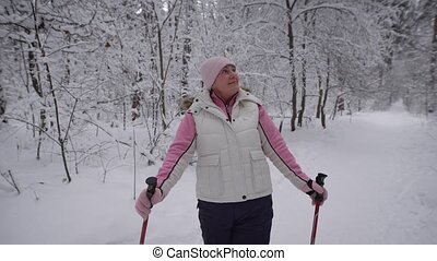 Energetic woman having nordic exercising in the forest.Happy female athlete standing with ski poles on the path in winter nature outdoors and looking around pleased with walking and healthy lifestyle.