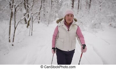 Energetic woman in warm white waistcoat and black trousers doing active nordic walking exercising in the forest. Female athlete stepping quickly with ski poles on the path in winter nature outdoors.