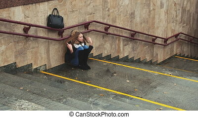 Young girl on the stairs in the subway depressed sitting...
