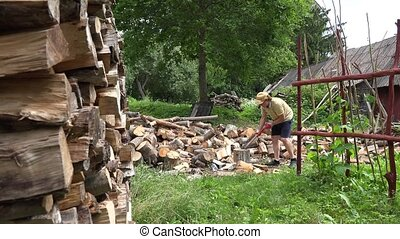 Peasant man in shorts prepare firewood. 4K - Strong peasant...