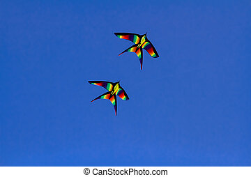 Colorful kites flying isolated on blue background
