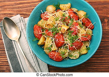 Fried potato and tomato salad with cheese