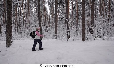 Side view of active woman with rucksack doing nordic walking in the forest. Retired lady stepping quickly with ski poles on the path in winter nature outdoors demonstrating healthy lifestyle.