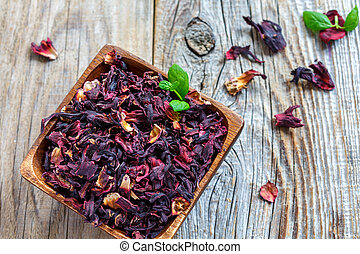 Red Hibiscus tea in a square wooden bowl.