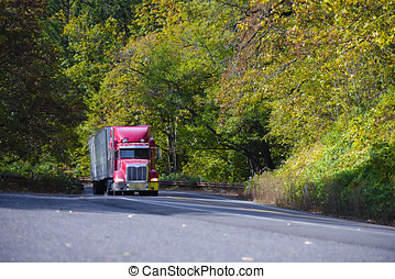 Red modern semi truck with trailer going up hill in autumn...