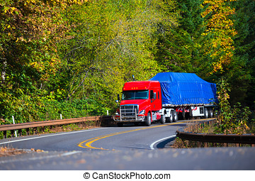 Red semi truck flat bed trailer on winding autumn highway -...