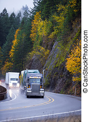 Long haul Semi trucks convoy in rain autumn windnig road