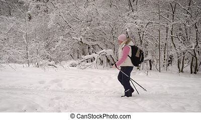 Side view of active woman dressed in warm white waistcoat and black trousers doing nordic walking quickly with ski poles on the path in winter nature outdoors, demonstrating healthy lifestyle.