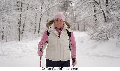 elderly woman in a beautiful sports wear is engaged in Nordic walking