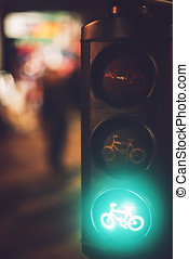 Close up crop traffic lights with bicycle sign burning in green colour on blurred background.