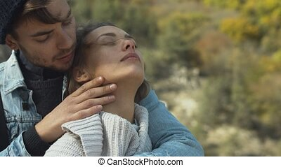 Couple in love in the forest hugging and relaxed, close up
