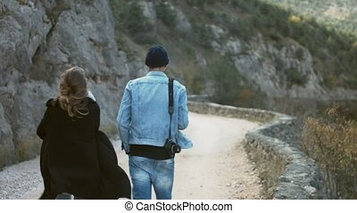 Hipster couple in love walk along forest road