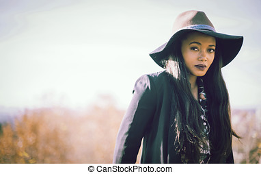 Portrait of black female leaning on fencing - Portrait of...