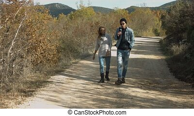 Young couple holding hands and walking along forest road