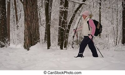 The woman in ski tracks a suit in the wood. The pensioner by...