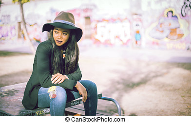 Black Female sitting on table outdoors in urban environment...