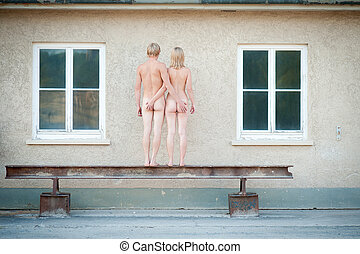 Nude of a sexy young couple, rear view in front of a house...