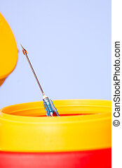 Yellow medical disposal waste box, syringe needle with red drop on the tip