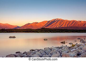 Long exposure landscape view of Lake Tekapo and mountains,...