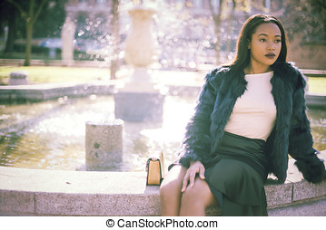Female sitting near fountain - Front view of young stylish...