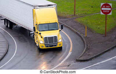 Yellow semi truck and reefer trailer turn on highway exit -...