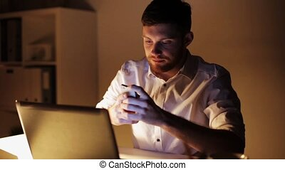 man with laptop and smartphone at night office - business,...