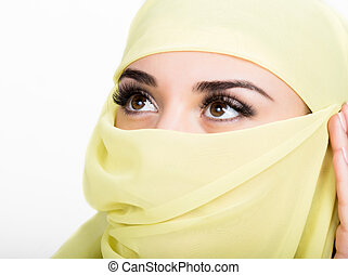 Asian girl with brown eyes posing in a yellow scarf,...