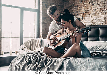 Teaching her to play guitar. Handsome young bearded man teaching his girlfriend to play guitar while both sitting in bed at home together