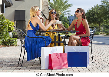Three Beautiful Young Women Having Coffee With Shopping Bags...