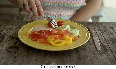 Woman eating salad at resort