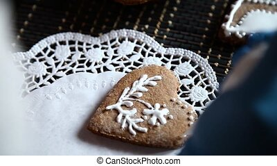 Female hands decorating gingerbread stocking with icing sugar using selfmade pastry bag