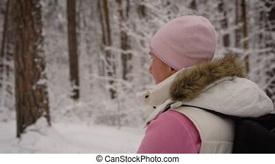Side view of a woman  bit tired. On her head pink hat, also she is dressed in  white waistcoat,  light jacket, gray pants. In  hands have ski poles with  sharp tip to make it easier  walk in the snow