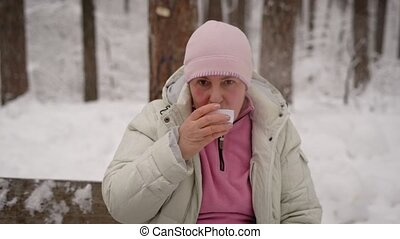 Elderly woman drinking hot tea while sitting on a bench in  snow-covered park. Grandmother after walk in the fresh air, sat down to rest beside the table  which stands the drink.