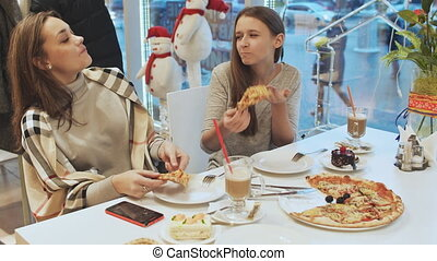 Two young schoolgirls friends eating pizza and talking in a cafe fun. In the background view of a city street. Autumn, Winter.