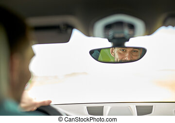 rearview mirror reflection of man driving car - road trip,...