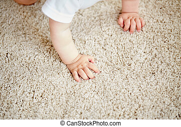 hands of baby crawling on floor or carpet