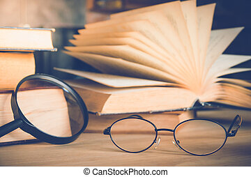 Reading glasses and magnifying glass with olds book on table