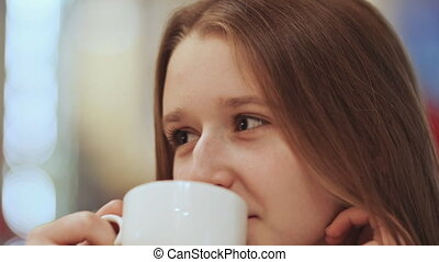 Close-up face of young beautiful schoolgirl, drinking coffee...