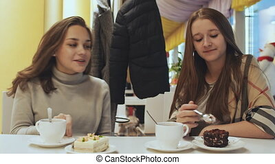 Two young schoolgirl girlfriends in a cafe drinking coffee and eating pastries. Autumn, Winter.
